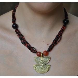 Collier rouge avec un pendentif en bronze par Rasmata Ouédraogo